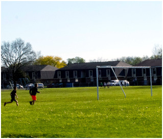 Two children playing on a soccer field